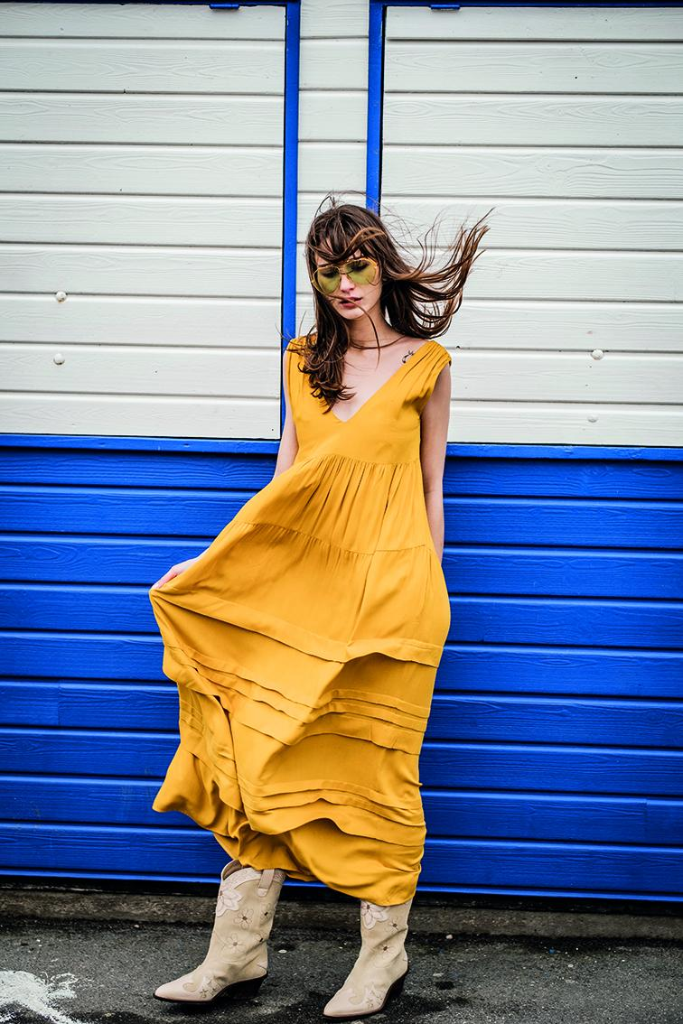 White woman standing wearing mustard yellow sleeveless dress with gathered tiers and horizontal pleats on the skirt.