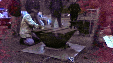 Photo: Michael Wittman clamps the lid down onto the pyramid kiln for a dry quench.