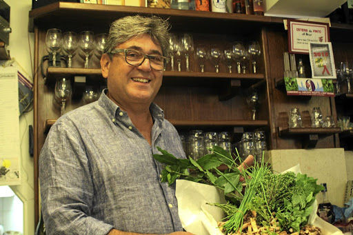 Francesco Pinto, grandson of the original owners of the All'Arco snack bar in Venice, displays fresh herbs, which will be used in the day's dishes. Picture: MADELEINE MORROW