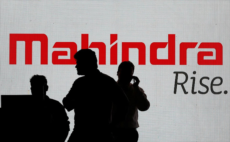 People walk past a screen displaying Mahindra and Mahindra logo in Mumbai, India. Picture: REUTERS/DANISH SIDDIQUI