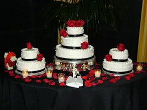 Photo: 3-tier wedding cake w/two 2-tier side cakes. Decor features smooth whipped cream icing with triple dot clusters & black satin ribbon wrap on each tier. Red roses provided by florist to add the finishing touches.
