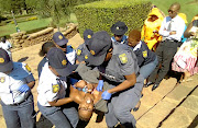 Gugu Ncube is arrested during her  naked solo protest at the Union Buildings. The writer is critical of the heavy-handed approach by the police during the arrest.