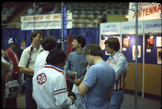 Photo: W2SQ and K5GN hobnob with K1GQ manning the Cushcraft booth at Dayton 1982.  Looks like K1AR in the foreground wearing the blue tee shirt.