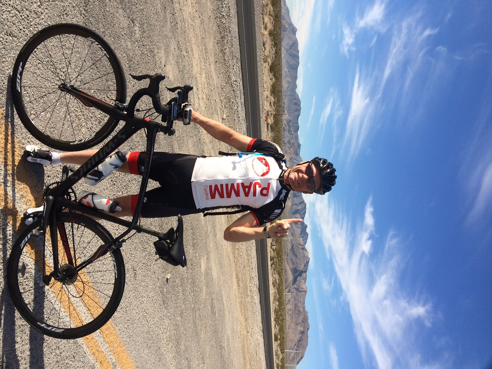 John Johnson PJAMM Cycling with bike on Kyle Canyon Hwy 157 Mt Charleston bike climb.