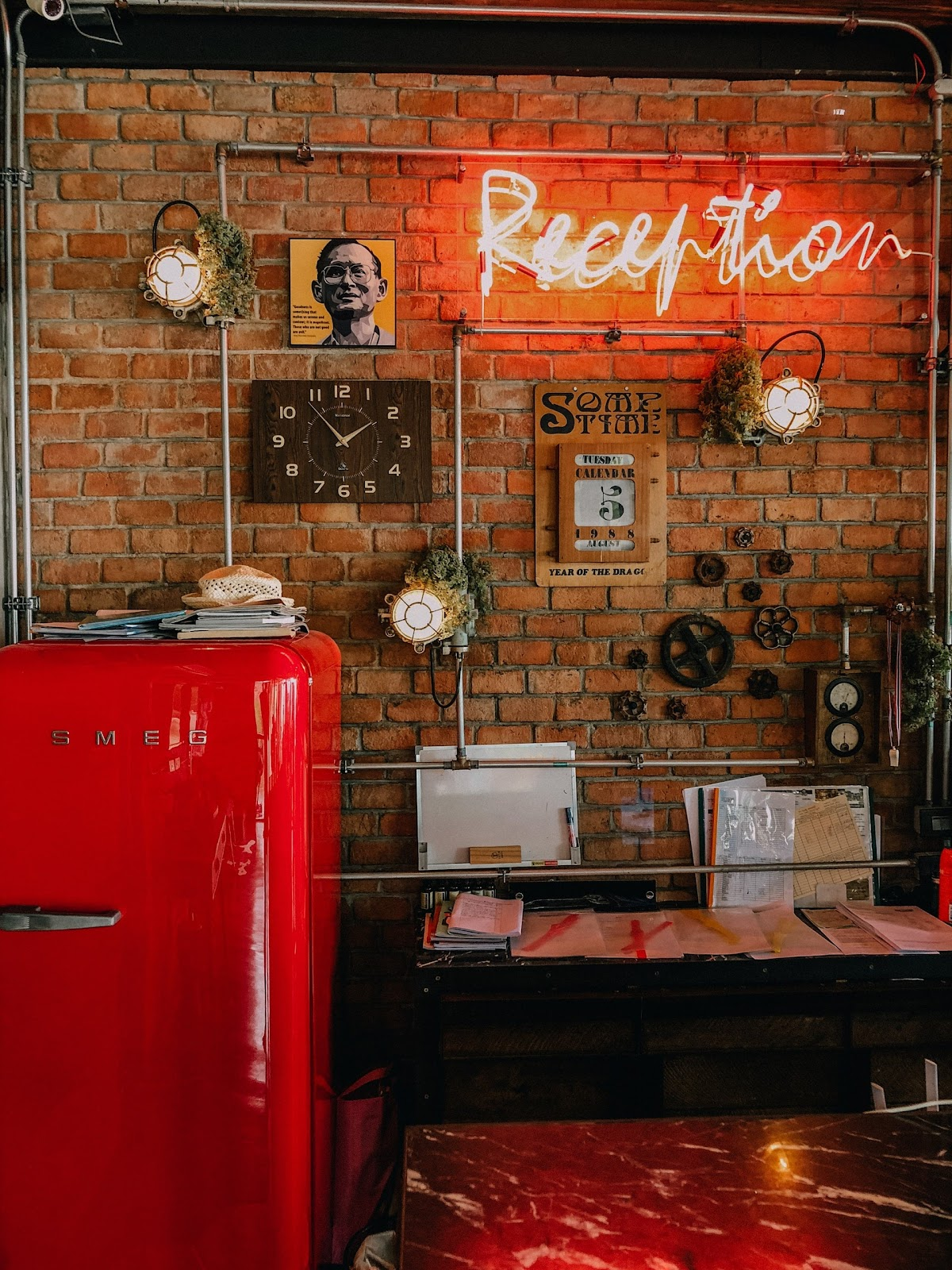 Retro appliances can instantly help in creating vintage kitchen designs; a bright red refrigerator placed in front of a brick wall decorated with bold artistic pieces