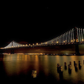 S.F. Bay Bridge Lights Up at Night by Kim Wilson - Buildings & Architecture Bridges & Suspended Structures ( illuminated, famous, photograph, exterior, reflections, travel, landscape, attraction, pwcbridges, lights, dark, san francisco, evening, water, clouds, picturesque, california, image, suspension, pylons, landmark, bay, horizontal, outdoors, night, bridge, outside, span )
