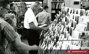 Photo: Wilkinson looking through greeting cards. The date and location of this photo are not known.