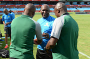 Mamelodi Sundowns head coach Pitso Mosimane (C) shakes hands with Bloemfontein Celtic co-coaches John Maduka (L) and Lehlohonolo Seema (R) during the Absa Premiership match at Loftus Versfeld in Pretoria on March 02, 2019.