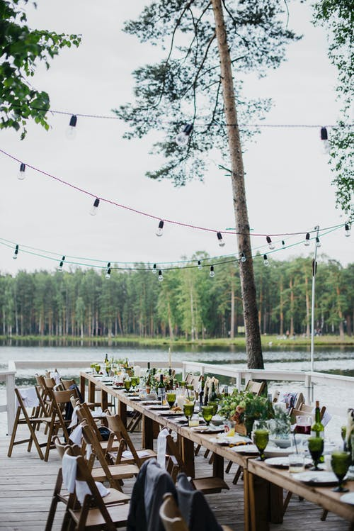 Wooden terrace with green trees and tables located near lake preparing for festive romantic party in nature under blue sky