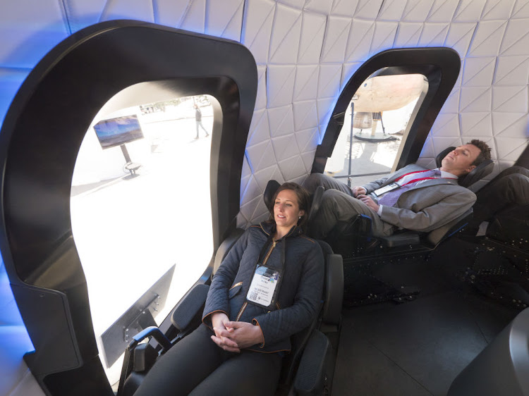 Attendees sit inside the high fidelity crew capsule mock up of the Blue Origin New Shepard system during the Space Symposium in Colorado Springs, Colorado, U.S., on Wednesday April 5 2017.