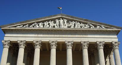Photo: A bejáratnál sorakozó nyolcoszlopos oszlopcsarnok felett elhelyezkedő timpanonban, az olimpiai Zeusz templom szoborcsoportjának a mása látható