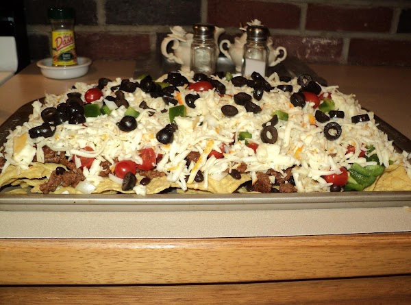 Next, Sprinkle meat over the tortilla chips, then layer with black beans, onion, tomato...