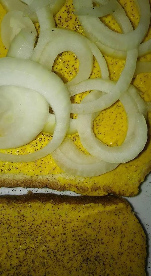 Put the slices of onion on top of mustard and black pepper.