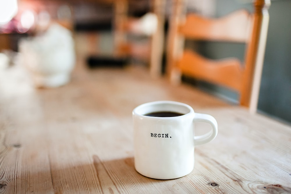 white ceramic mug on table for morning routine coffee