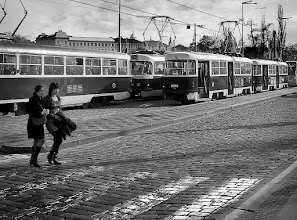 "Photo: Streetcars In Prague February 2008  After a morning of wandering around St. Vitus Cathedral and the Prague Castle complex, we made our way down the sloping road toward the tourist district. At the bottom was an intersection of streets and rail lines that seemed an attractive photo subject.  Just as I pressed the shutter two women walked into my frame- and to be honest, I wasn't paying too much attention, because my travel partners were heading away quickly, looking for lunch! Only later did I see the women in the shot, and thought, ""If only I had waited three steps, they would have been on the 'rule of thirds' line."" Oh well, right?  I have posted versions of this before, and at the time I thought they were pretty good. Yet later, I realized that the vignette was too heavy handed and actually distracted from the positive qualities about the shot. A few years have gone by and I now have the tools in #PhotoshopCC  and #LightroomCC  along with some other plugins to improve my production.  The original b/w conversion may have included Topaz B&W Effects, but I don't really remember. This time around I used #TopazRemask  to select the empty white sky so I could add some clouds. That allowed me to add a subtle vignette that almost isn't there, unless you really know what you're looking for.  Just because I don't mind people seeing before and after comparisons when I re-work a picture, I'll leave the old version in the album (https://goo.gl/121e5J ) but I've removed the original post from the Prague - February 2008 collection.  #Travel   #CzechRepublic   #Prague"
