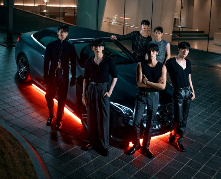 A group of men standing next to a car with its doors open  Description automatically generated with medium confidence