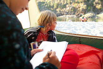 Photo: Young girl writing in journal while on a whitewater raft trip on the Main Salmon River in central Idaho