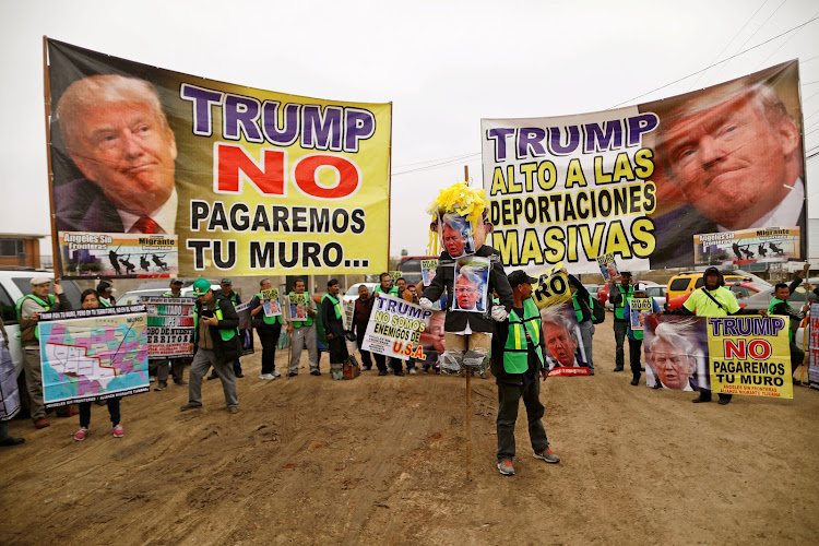 People hold signs reading 'Trump, we will not pay for the wall' and 'Trump, stop the mass deportations' near the border fence between Mexico and the US in Tijuana, Mexico.