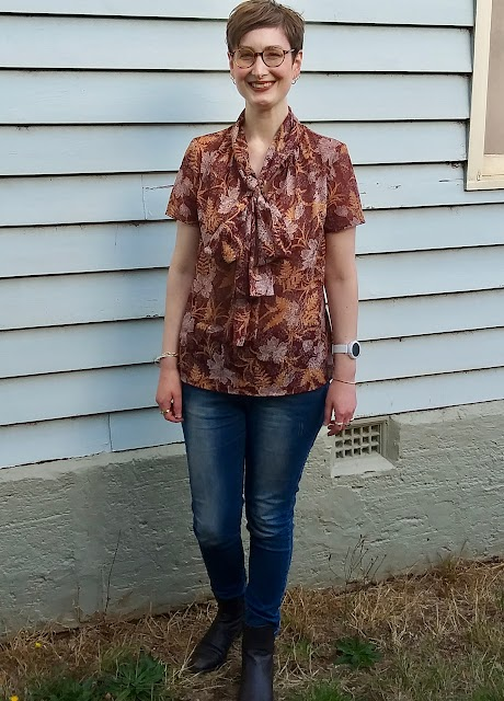 Siobhan stands in front of a blue weatherboard wall. She wears an earthy brown, fern-print short sleeve blouse with comically large bow at neck, blue slim jeans and brown boots. She is smiling.