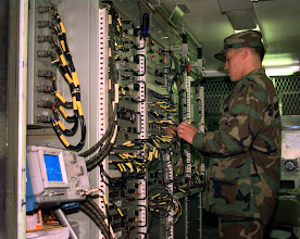 Photo: Operating a satellite communications truck, Pfc. Kurt S. Bearchum, Company B, 112th Special Operations Signal Battalion (Airborne), checks all wiring connections during his shift.  The battalion was the communications hub for the Joint Special Operations Task Force headquarters and participating units at Camp Blanding, Fla., during exercise Purple Dragon '98.
