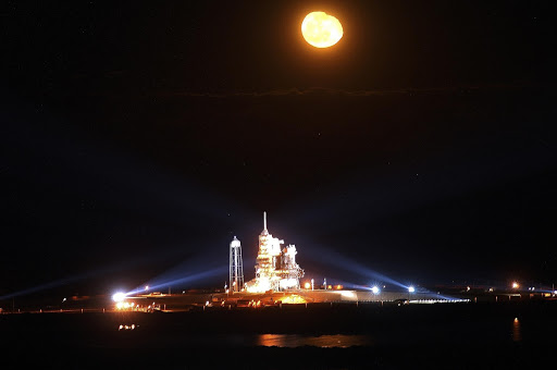 A full moon over Kennedy Space Center competes for dominance in the night sky poised for launch from Launch Pad 39A.