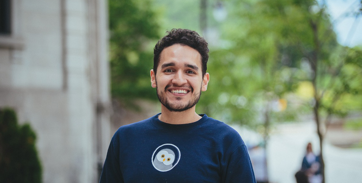 Founder, Jose, smiles in front of a tree lined street.