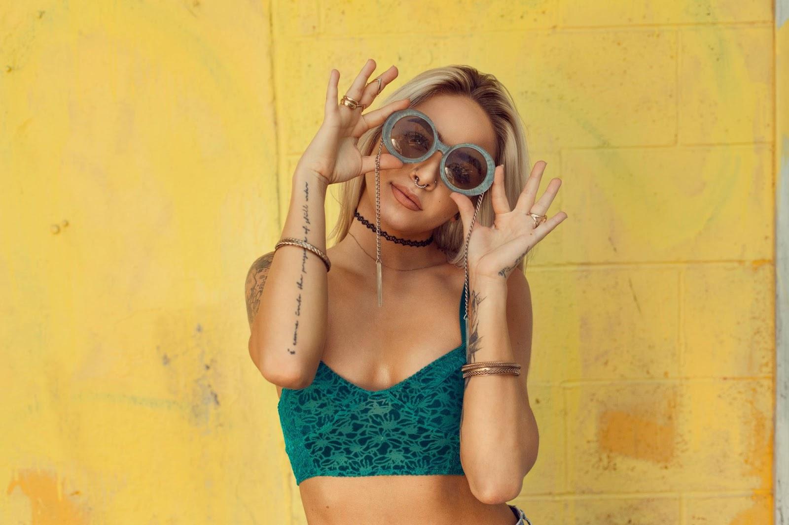 ragazza-bionda-che-tiene-in-mano-occhiali-da-sole