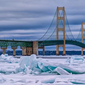 Blue Ice Under the Bridge by Carol Ward - Buildings & Architecture Bridges & Suspended Structures ( michigan, winter, lake michigan, blue ice, ice, lake huron, winterscape, mackinaw city, architecture, frozen, landscape, bridges, mackinac bridge )