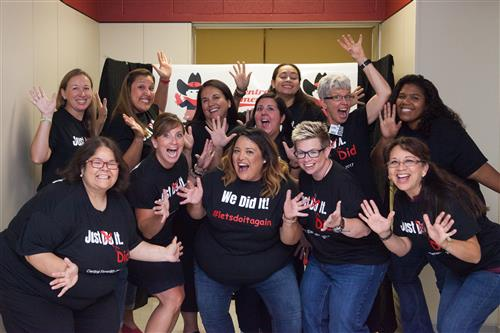 Maria Luna and other teachers crowd together, celebrating with big smiles and big jazz hands