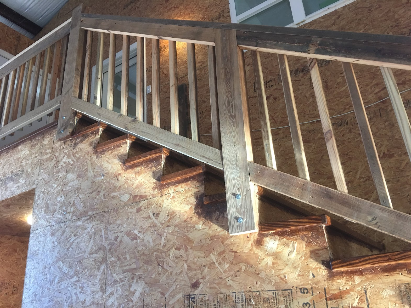 rustic farmhouse staircase with reclaimed lumber handrails