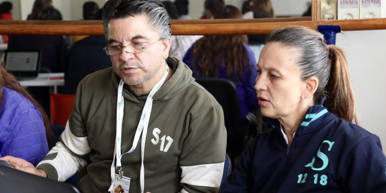 Dos personas adultas observan atentamente la pantalla de un Chromebook.