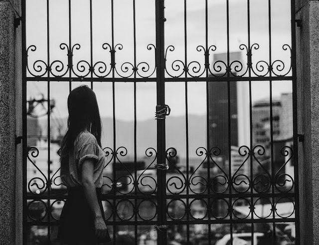 イメージ写真。塀越しに女性が街を見ている