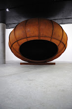 "Photo: This piece - ""Cave (2012)"" - is one large indoor exhibition. It is Kapoor's most recent Cor-Ten steel work. A massive oval steel structure weighing 13 tons is balanced on top of an iron rod. The resulting form  which appears to be perched lightly on the ground - overturns the viewer's usual conception of weight and balance and one feels uneasy in front of it. Despite the fact that the work itself has a rough finish, with a very tangible materiality, it has a subtle psychological impact. A shadow is cast over the heads of those standing before it, which inspires in the viewer a paradoxical mixture of excitement and fear.