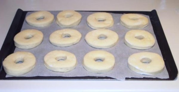 With a spatula, place the cut-out doughnuts on parchment lined or floured cookie sheets;...