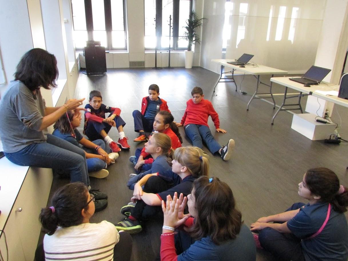 Alumnes escoltant les instruccions de la monitora per a la realització del taller fotogràfic.