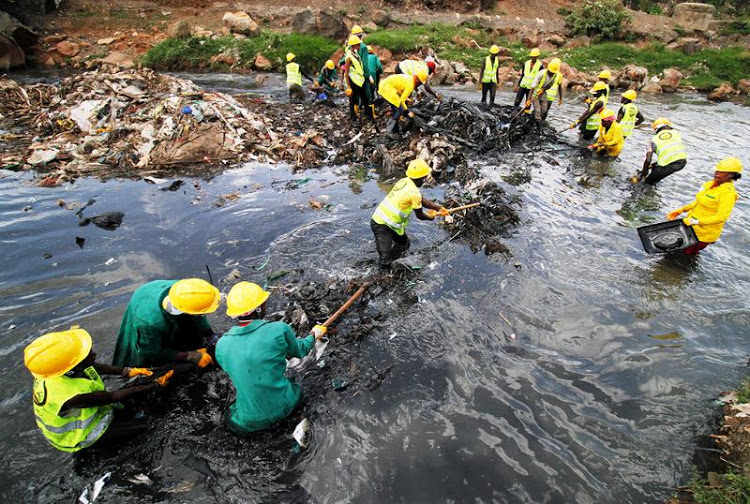 Hired youths clean up Nairobi River in Dandora on May 15, 2019. The river can no longer sustain life.