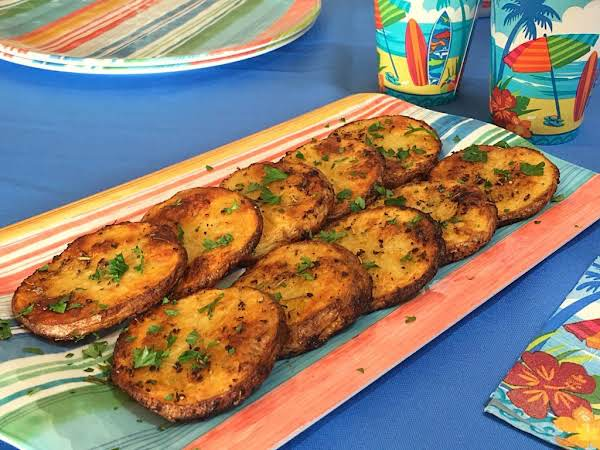 Slices Of Potatoes Sprinkled With Chopped Parsley On A Serving Plate.