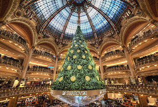 """Photo: Christmas in the City of Lights  This is one of the most awesome Christmas trees I've ever seen! Sure, it's bathed in a sea of rampant commercialism, but, like a Russian friend said, """"It is what it is.""""  I wonder if there is a """"Making Of"""" for this tree inside the Galaries Lafayette in Paris. The entire thing is suspended in midair! I'd love to see how they get this giant tree inside and hang it every year. It must take forever, since the French are only legally allowed to work 12 hours per week.  (See full rez 7168x4883) athttp://goo.gl/OxN4K"""