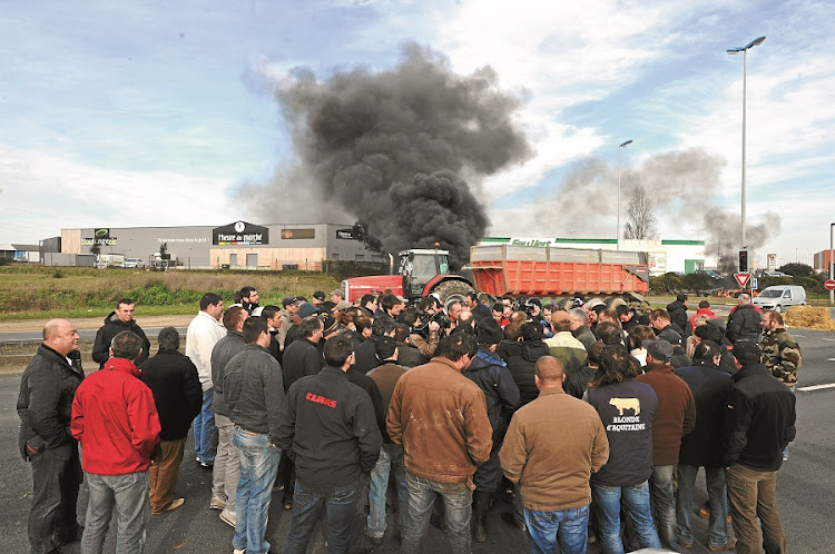 About 100 pig and dairy farmers bring part of the port of la La Rochelle in France to a standstill, with the help of about 40 tractors used to block roads. The farmers protested against the falling prices of their products. Picture: GALLO IMAGES/AFP/