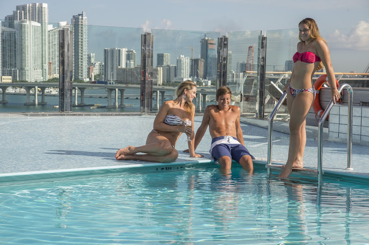 A family soaks up the sun on the pool deck