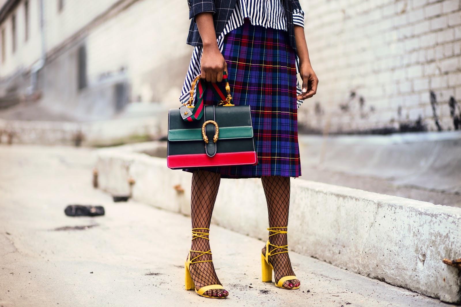 דוגמנית עם גרבי רשת, תיק ביד, לבושה בחצאית עם צבעים