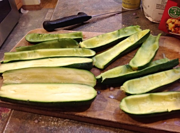 With a medium size spoon, remove the centers of each zucchini, and add it...