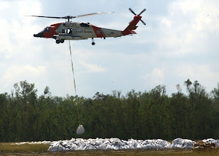Photo: 051001-N-8253M-003: Naval Air Station Joint Reserve Base New Orleans, Louisiana (October 1, 2005)--United States Coast Guard working in conjunction with Army Engineer Bravo Company 205th Army National Guard, transports 16,000 pound sandbags to Southern Plaqueminne's Parish region to repair broken levees caused by Hurricane Rita.