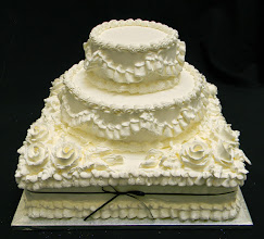 Photo: Multi-textured wedding cake (square base w/round middle & top tiers) featuring ribbon borders on sides w/traditional top & bottom borders. Thin black ribbon bow tied around bottom tier w/whipped cream frosting roses on top.