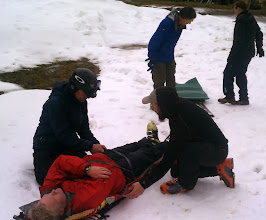 Photo: Mark being tended to by his students. After the sled testing, we skinned up the ski area into the soupy weather, practicing efficient skinning strides and tricky kick turns. And finally, the class was dismissed to enjoy some wet snow turns back down the base -- many thanks to everyone for a safe, fun, and productive course!