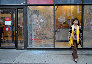 Photo: A woman walks away after inspecting the damage done to a Scotia Bank near Queen Street West and John Street.