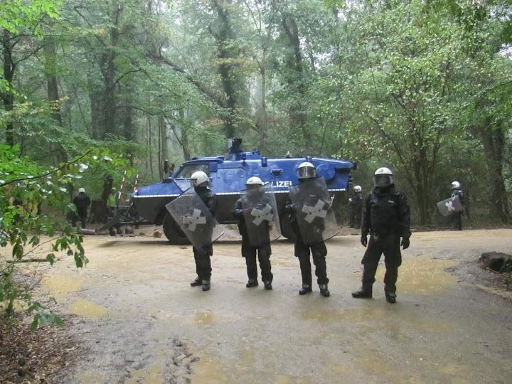 Polizei mit Helm und Schild, hinten Panzerfahrzeug.