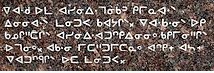 Glyphs of the Western Cree on a speckled stone background.