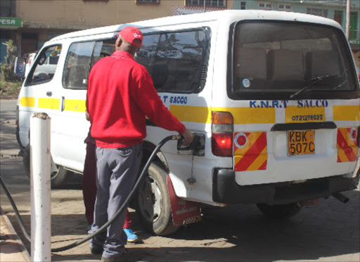 Going up already? A Total Station attendant fuels a matatu in Ngara, Nairobi, on January 15.