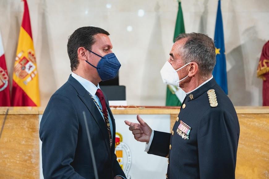 El orador, el coronel Javier Soriano, habla con el presidente de la Diputación, Javier A. García.